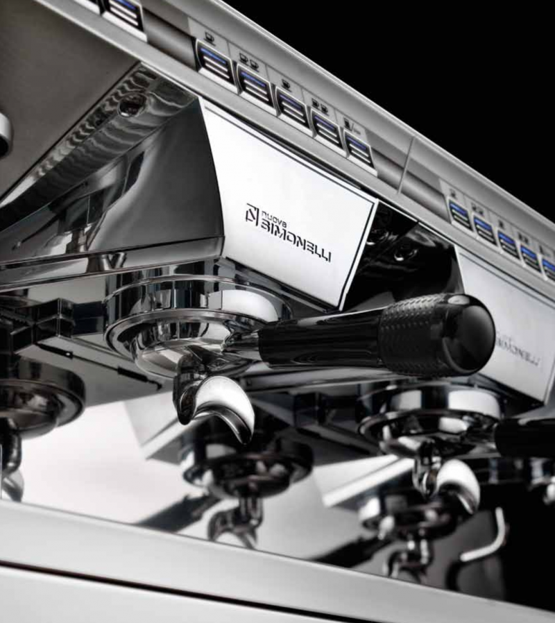 This image is a closeup view of the Nuova Simonelli Appia II brew group, with traditional brew group height and volumetric dosing controls.