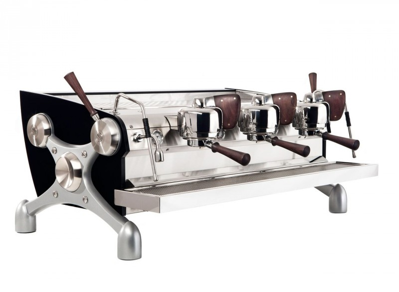 This image is a front-side view of the Slayer Espress machine powder coated black with peruvian walnut accents, 3 groups at traditional height and manual dosing controls.