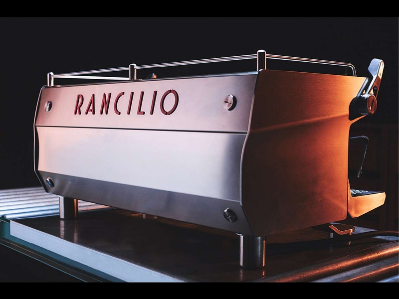 This image is a back-side view of the Rancilio Specialty RS1 3 group espresso machine in Stainless Steel.